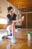 Во всю длину женского баскетболиста используя мобильный телефон Стоковые Изображения RF