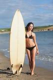 Во всю длину женщины бикини держа surfboard на пляже Стоковое Изображение