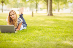 Во всю длину женщины используя компьтер-книжку пока лежащ на траве Стоковая Фотография