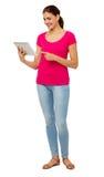 Во всю длину женщины используя таблетку цифров Стоковое Изображение