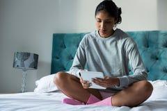 Во всю длину женщины используя цифровую таблетку на кровати Стоковые Изображения