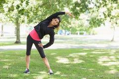 Во всю длину здоровой женщины делая протягивающ тренировку в парке Стоковые Изображения RF