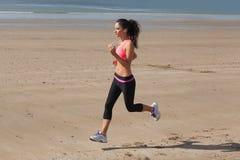 Во всю длину здоровой женщины jogging на пляже Стоковое Фото