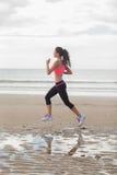Во всю длину здоровой женщины jogging на пляже Стоковые Изображения RF