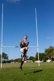 Во всю длину игрока рэгби скача для того чтобы уловить шарик против голубого неба Стоковое фото RF