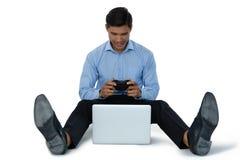 Во всю длину молодого бизнесмена играя видеоигру на компьтер-книжке Стоковое фото RF
