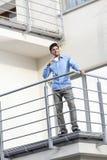 Во всю длину молодого бизнесмена имея кофе на балконе гостиницы Стоковая Фотография