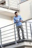 Во всю длину молодого бизнесмена имея кофе на балконе гостиницы Стоковые Изображения