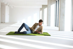 Во всю длину молодого бизнесмена используя планшет пока возлежащ на дерновине в офисе Стоковая Фотография RF