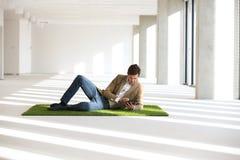 Во всю длину молодого бизнесмена используя цифровую таблетку пока возлежащ на дерновине в офисе Стоковые Фотографии RF