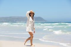 Во всю длину молодой женщины идя на пляж с шляпой Стоковое Изображение RF