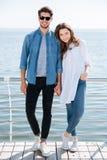 Во всю длину молодой пары стоя совместно держащ руки Стоковые Фото