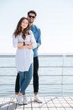 Во всю длину молодой пары стоя совместно обнимающ Стоковая Фотография RF