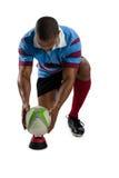 Во всю длину мужского игрока рэгби держа шарик на тройнике Стоковое фото RF