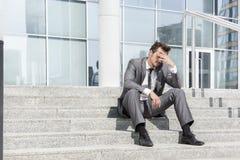 Во всю длину подавленного бизнесмена сидя на шагах вне офиса Стоковая Фотография RF