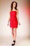 Во всю длину привлекательной курчавой девушки женщины в красном платье на пинке Стоковые Фото