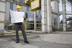 Во всю длину светокопии молодого мужского архитектора рассматривая вне индустрии стоковое фото