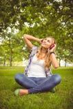 Во всю длину счастливой женщины наслаждаясь музыкой на парке Стоковые Фото