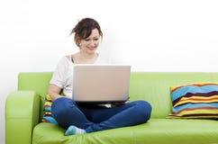 Во всю длину счастливой молодой женщины используя компьтер-книжку пока сидящ на зеленой софе Стоковое Фото