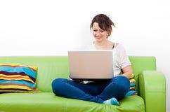 Во всю длину счастливой молодой женщины используя компьтер-книжку пока сидящ на зеленой софе Стоковые Изображения RF