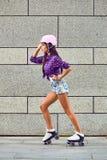 Во всю длину счастливый кататься на коньках ролика молодой женщины стоковое изображение rf