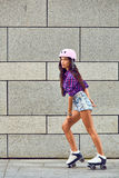 Во всю длину счастливый кататься на коньках ролика молодой женщины стоковые изображения