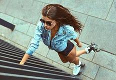 Во всю длину счастливый кататься на коньках ролика молодой женщины стоковая фотография rf