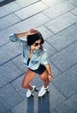 Во всю длину счастливый кататься на коньках ролика молодой женщины Стоковое Изображение
