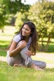 Во всю длину усмехаясь женщины сидя на траве в парке Стоковая Фотография