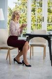 Во всю длину усмехаясь коммерсантки держа кофейную чашку в кафе Стоковые Изображения