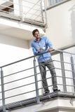 Во всю длину усмехаясь молодого бизнесмена имея кофе на балконе гостиницы Стоковая Фотография RF