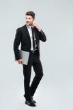 Во всю длину усмехаясь молодого бизнесмена с компьтер-книжкой Стоковая Фотография