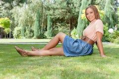 Во всю длину усмехаясь молодой женщины ослабляя на траве в парке Стоковые Изображения