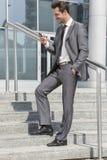 Во всю длину усмехаясь обмена текстовыми сообщениями бизнесмена через сотовый телефон пока стоящ на шагах вне офиса Стоковое Изображение RF