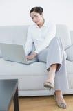 Во всю длину хорошо одетой женщины используя компьтер-книжку на софе Стоковое фото RF