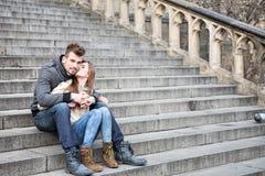 Во всю длину любящей женщины целуя человека пока сидящ на шагах outdoors Стоковое Фото