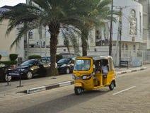 Водители желтых tuks tuk курсируют их торговлю вокруг портового города Стоковая Фотография