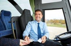 Водитель автобуса при деньги продавая билет к пассажиру стоковые фотографии rf