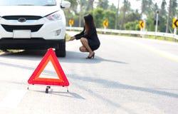 Водитель бизнес-леди изменяя на ее сломленном автомобиле Стоковая Фотография RF