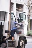 Водитель взбирается лестницы semi для того чтобы перевезти кабину на грузовиках Стоковые Фото