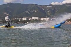 Водитель вода мотоцикла воды брызгает банана пассажиров раздувного Деятельности при пляжа в заливе Gelendzhik Стоковое Изображение