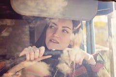 Водитель грузовика женщины в автомобиле Девушка усмехаясь на камере и держа рулевое колесо Стоковые Изображения RF