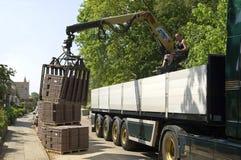 Водитель грузовика, построитель дороги разгржает камни грузовика вымощая Стоковые Фотографии RF