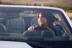 Водитель девушки ковбоя в белом автомобиле с откидным верхом Стоковое фото RF
