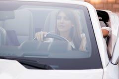 Водитель девушки сидит за колесом автомобиля с откидным верхом Стоковое фото RF