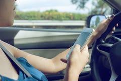 Водитель женщины используя умный телефон Стоковая Фотография