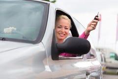 Водитель женщины показывая ключи автомобиля стоковые изображения