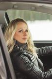 Водитель женщины сидя в черном автомобиле Стоковые Фото