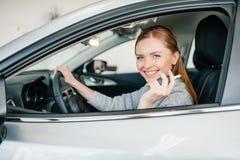 Водитель молодой женщины сидя в новом автомобиле и держа ключ Стоковые Изображения RF