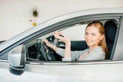 Водитель молодой женщины сидя в новом автомобиле и держа ключ Стоковые Изображения